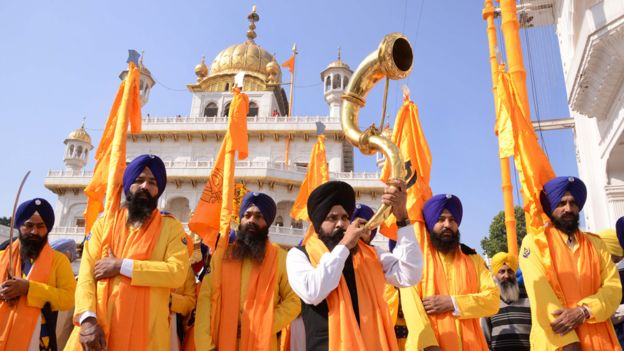An Indian Sikh devotee plays a musical instrument as he walks with Punj Pyara holding flags