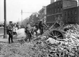 HL 5241 Britse soldaten doorzoeken puinhopen van het door opstandelingen in brand gestoken Kavanagh Public House in Bridge Street bij de Paasopstand in Ierland 1916.