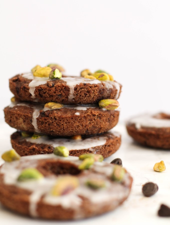 Chocolate Pistachio Donuts that are vegan, gluten free, refined sugar free, and delicious! Filled with flavor, chocolate, and natural sweetness, these make for a great dessert or snack.