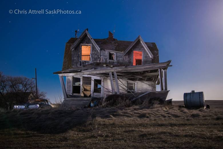 Abandoned house lit with orange lights at night.
