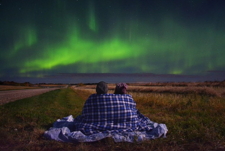 Photo of a couple cozying up together under a blanket while watching the northern lights dance over an open field.