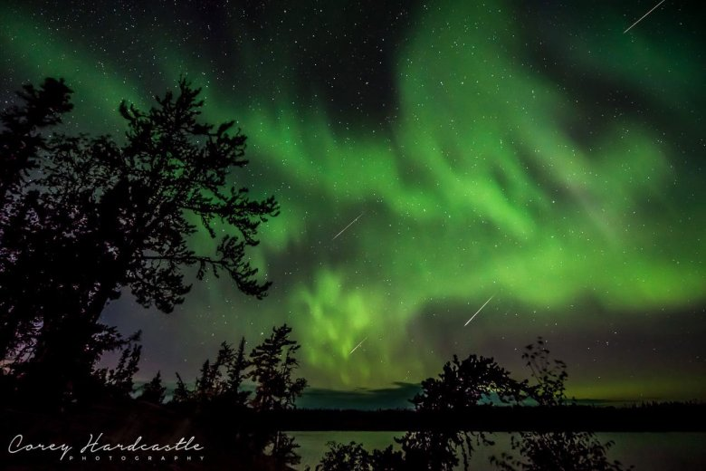 Green northern lights dancing over a lake with three meteors flashing through the sky.