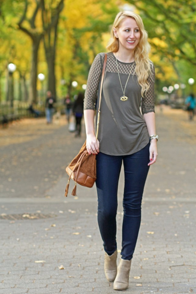 Wearing olive crochet top, jeans, brown bucket bag, and taupe ankle boots for fall in Central Park