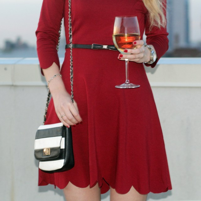red dress worn with a bow belt and striped bag