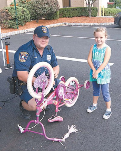 Photo by Karen Zautyk Officer Jack Corbett etches bike for tyke at last year's fair.