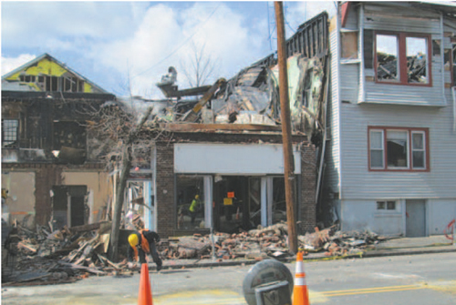Aftermaths: (Above) Demolition begins on Harrison buildings destroyed in March fire.