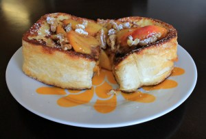French Toast on a colorful flowered plate with fresh peaches and walnuts