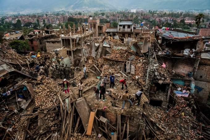 5—Bhaktapur, Nepal. Wednesday, April 29, 2015: Residents forage through their destroyed homes, gathering salvageable belongings on April 29, 2015 in Bhaktapur, Nepal. On the 25th of April, just before noon local time, as farmers were out in fields and people at home or work, a devastating earthquake struck Nepal, killing over 8,000 people and injuring more than 21,000 according to the United Nations Office for the Coordination of Humanitarian Affairs. Homes, buildings and temples in Kathmandu were destroyed in the 7.8 magnitude quake, which left over 2.8 million people homeless, but it was the mountainous districts away from the capital that were the hardest hit. Villagers pulled the bodies of their loved ones from the rubble by hand and the wails of grieving families echoed through the mountains, as mothers were left to bury their own children. Over the following weeks and months, villagers picked through ruins desperate to recover whatever personal possessions they could find and salvage any building materials that could be reused. Despite relief teams arriving from all over the world in the days after the quake hit, thousands of residents living in remote hillside villages were left to fend for themselves, as rescuers struggled to reach all those affected. Multiple aftershocks, widespread damage and fear kept tourists away from the country known for its searing Himalayan peaks, damaging a vital climbing and trekking industry and compounding the recovery effort in the face of a disaster from which the people of Nepal continue to battle to recover.