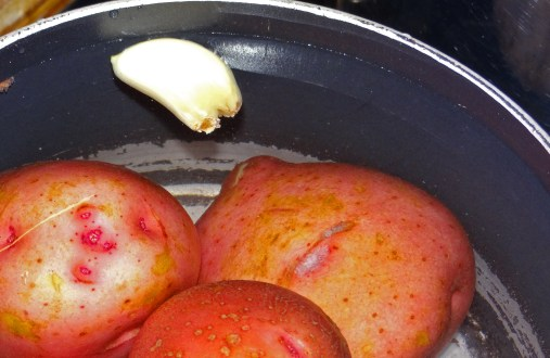 Add garlic into the potatos and salted water. Then turn on the burner to bring potatoes to a boil.
