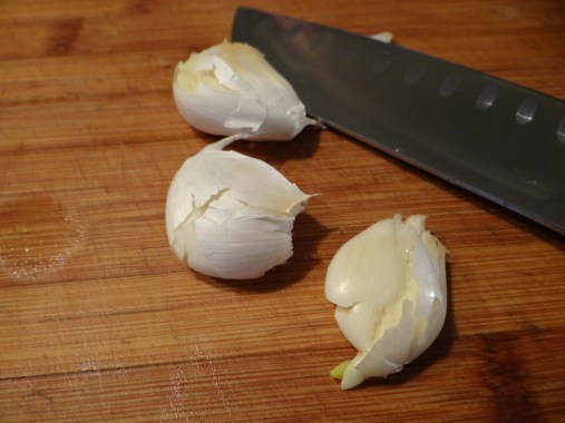 Crush some garlic with the flat of your knife.