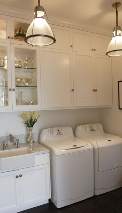 Laundry room with light fixtures and white cabinets