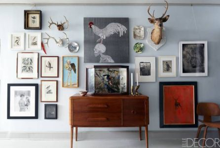 Eclectic wall of photos and taxidermy via Elle Decor