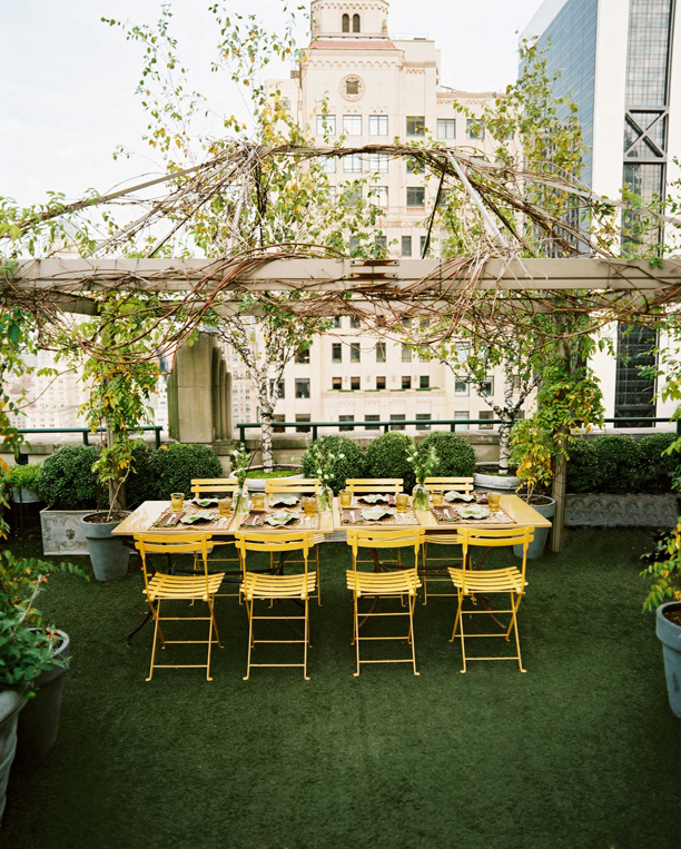 a fantastic rooftop space full of planters of boxwood and posh yellow chairs this tablescape area is by celerie kemble via lonny