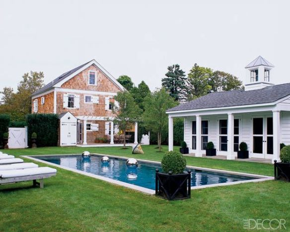 pool house surrounded by potted boxwood via Elle Decor