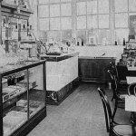 """A woman stands at the counter of a drug store sometime in the first half of 1925. Along the bottom row of the magazine rack on the right are copies of the pulp magazines """"Flynn's,"""" """"Blue Book,"""" """"Action Stories,"""" """"Love Story,"""" """"Breezy Stories,"""" """"Detective Fiction Weekly,"""" """"Snappy Stories"""" and """"Argosy All-Story Weekly."""""""