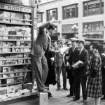 """Look carefully and you'll see that this man appears to be doing a dramatic reading from the March 1, 1927, number of """"Adventure"""" in this photo of a Los Angeles, Calif., newsstand. The newsstand displays for sale the March 5, 1927, number of """"Street & Smith's Western Story Magazine,"""" the April 1927 numbers of """"Ace-High Magazine"""" and """"War Stories,"""" and a """"Far West Stories."""""""