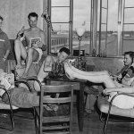 """Men with the Royal Air Force Volunteer Reserve take a break from training at the Graham Aviation Co. Flying School in Americus, Ga., on July 23, 1941. One of the men reads the Spring 1941 number of """"Exciting Sports,"""" while another reads the August 1941 number of """"Spicy Detective"""" with part of its cover carefully obscured."""