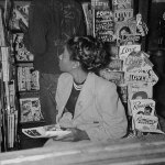 """A young woman waits at a comic book and magazine rack in late 1948. On display behind her are November 1948 numbers of """"Dime Detective Stories,"""" """"G-Men Detective,"""" """"Phantom Detective"""" and other pulps."""