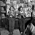 Two boys read comic books at a newsstand in September 1946. Pulp are stacked on the shelves along the left-side of the photo.
