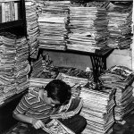 """While this kid is focused on the comics, a pulp fan would be looking through the stack of untrimmed pulp magazines just behind his right shoulder. There's a """"Dime Mystery"""" at the top of the stack. More pulps are stacked on the shelves above his head, including issues of """"Captain Future,"""" """"Planet Stories,"""" """"Blue Book,"""" and """"Western Tales,"""" but they are mixed in with a variety of other magazines. This photo of a used-magazine shop in Wellston, Mo., is from 1946."""