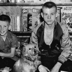 Two boys pose in front of a magazine stand in the summer of 1948. A number of pulp spines can be seen on the shelf at left.