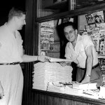 """No pulp covers are on display among the comic books and magazines in this newsstand in 1951, but there is a stack of pulps (with their spines facing out) on a shelf just between the two men. Titles include """"Best Sports,"""" """"New Love,"""" Smashing Detective Stories,"""" """"Fifteen Love Stories,"""" """"Fifteen Sports Stories,"""" """"Exciting Western,"""" and """"Famous Detective Stories."""""""