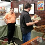 Rich Harvey looks through stacks of Argosy as Tim Cottrell looks on at the Bookery book store in Fairborn, Ohio. Numerous attendees made a pilgrimage to the store for 20% off.