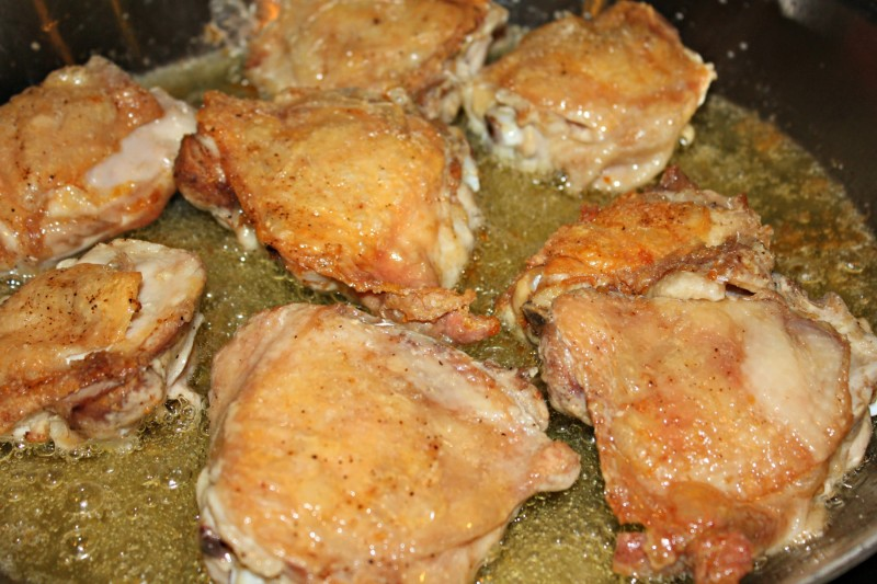 2200 chicken thighs browning in oil in pan