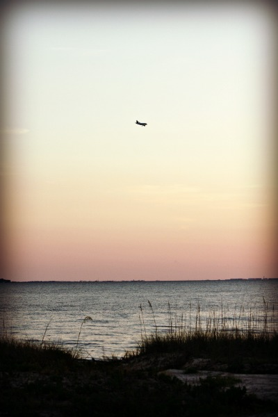Sitting on the beach, watching planes land. A serene moment away from emotional overload.