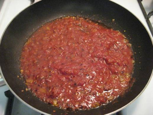 Adding the tomato sauce and past to the oil, onions, garlic, and red pepper flakes.