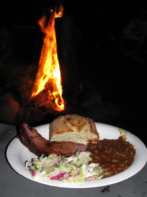 A side of Spicy BBQ Beans where they are happiest--on a plate with smoked beef brisket, cole slaw, and a hunk of bread, next to a roaring campfire!