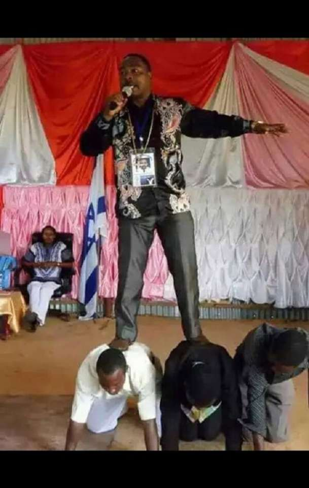 Pastor Sidney from Tanzania stands atop members to preach the sermon because he had a divine mandate not to allow his feet touch the ground | Facebook