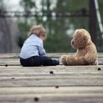 a baby boy playing with teddy bear