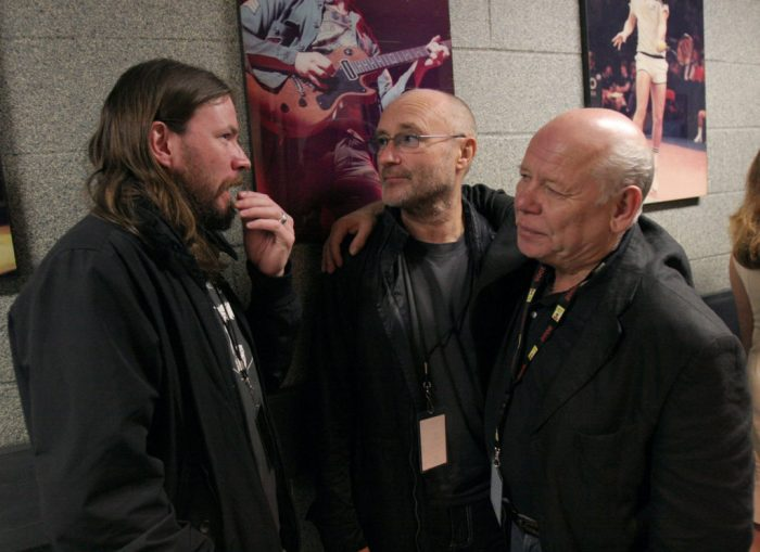 Onstage Sound Engineer Bob Pridden chats with Genesis drummer Phil Collins (middle) and another friend in the hallway backstage at Madison Square Garden following The Who's show.