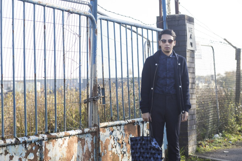 close up of Menswear blogger Ronan Summers modelling and styling a J. Lindeberg camo shirt and open cableknit jumper, and holds a Ports 1961 navy camo-star print tote bag