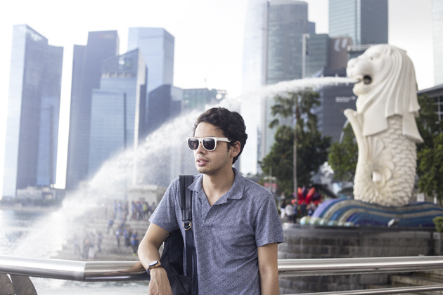 Ronan Summers wearing Felix Orlebar Brown polo shirt, and standing by the Merlion statue in Singapore