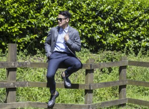 Ronan Summers wearing Hardy Amies fitted blazer  with a pair of tailored trousers and Givenchy squared sunglasses