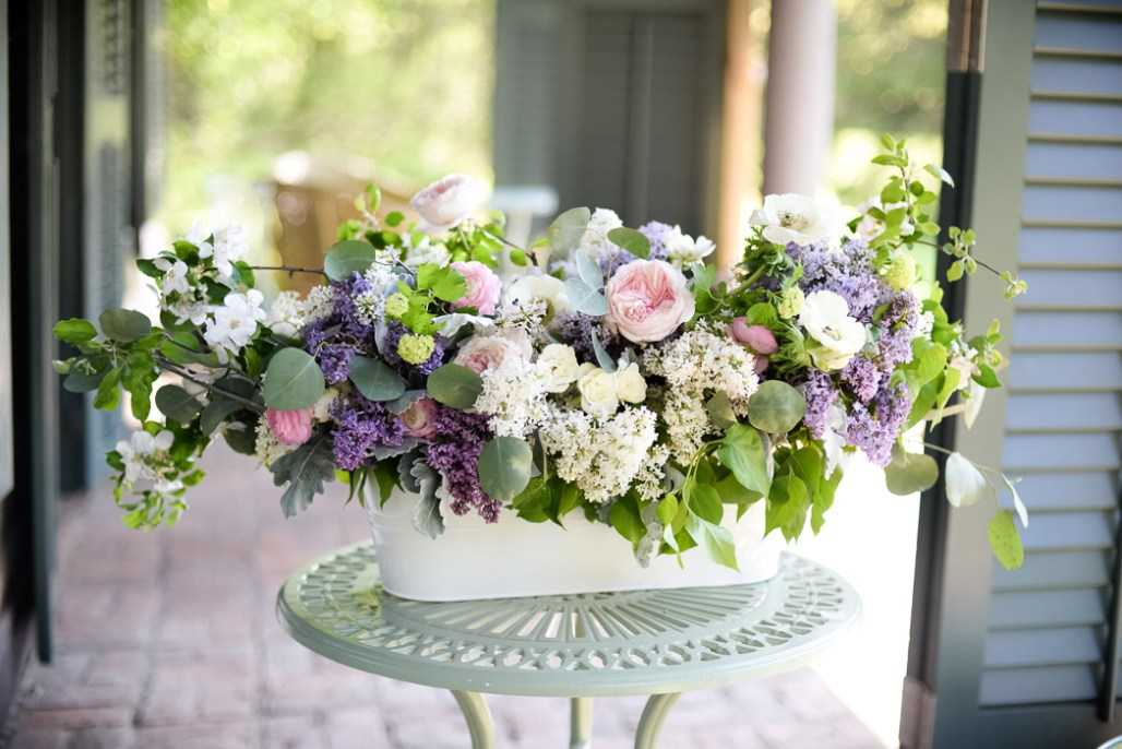 Large long flower arrangement featuring lilacs and garden roses