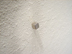 Use a magnet to find the studs or nails in your walls.