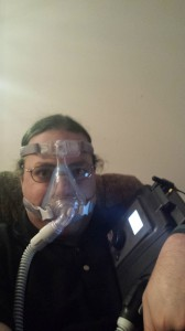 Me, wearing a full face mask, attached by a hose to a Philips BiPap system