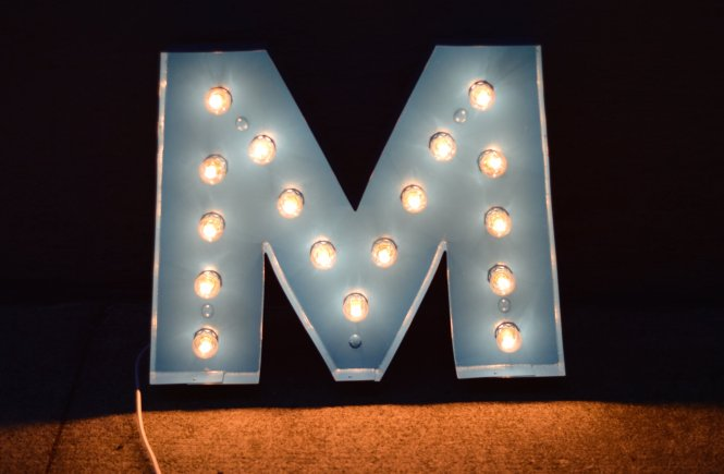 """Photo of the """"M"""" marquee sign lit up."""