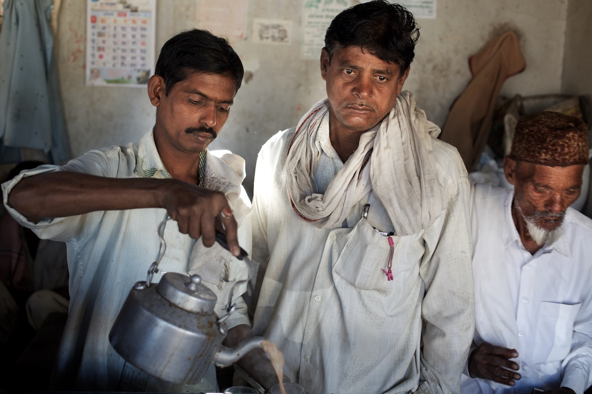 Farmers gather at a tea-stall in Adgaon Budruk village in Vidarbha, the cotton-growing district of Maharashtra state.   In 1991, the Indian Government liberalised its economy and launched a process of reforms that placed millions already poor farmers at the mercy of international markets. The Government's guaranteed purchase price for many Indian crops fell to a price-floor or were abandoned altogether. In Vidarbha, small-scale cotton producers who could once depend on a meagre but stable rate of return now regularly invest more money in the running of their farms than they generate in sales of cotton. This has necessarily forced many into debt, triggering uncertainty, destabilising lives and undermining development.  Photo: Tom Pietrasik January 2011 Maharashtra, India