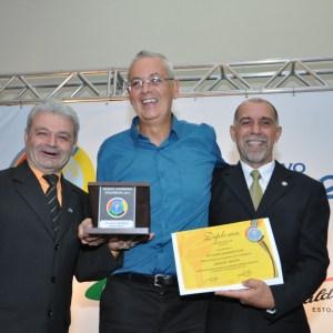 Ivo Bandeira (centro) recebe o Mérito Esportivo Panathlon 2015 do associado Adilson Mattos (esquerda) e do presidente do clube, Cláudio Esteves