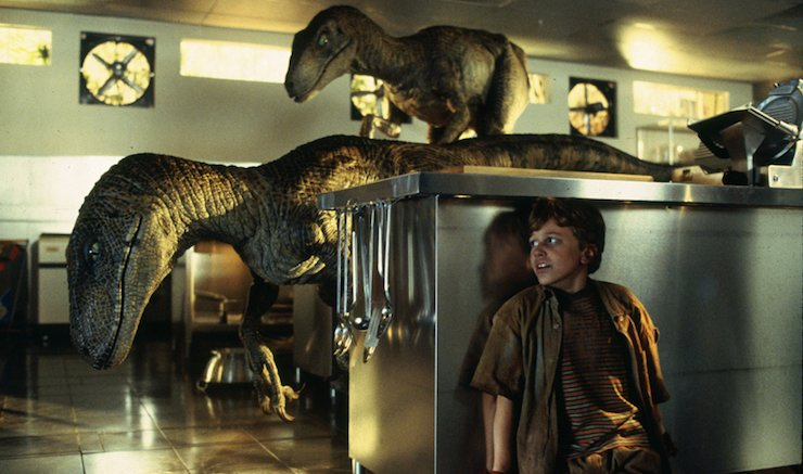 What role did greed play in the novel version of Jurassic Park?