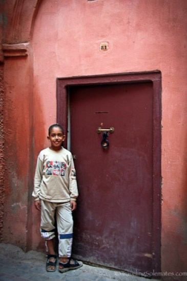 Boy standing by a door of a riad in Marrakesh