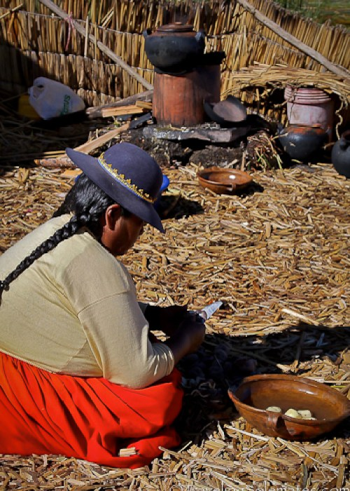 Woman cooking on Floating Island of the Uros, Lake Titicaca, Peru