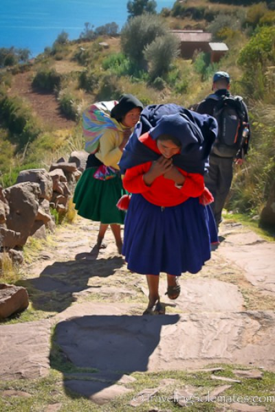 Women carrying heavy load on Taquile Island, Lake Titicaca, Peru