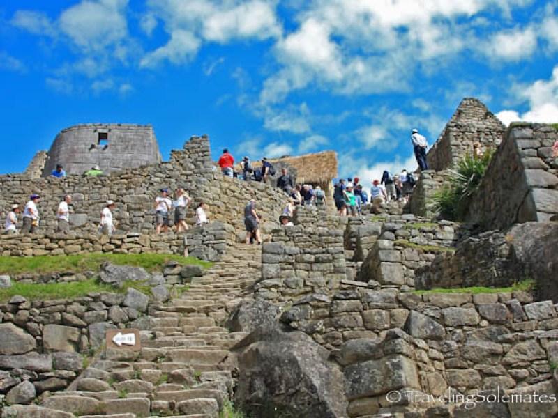 Visitors climbing the ruins in Macchu Picchu