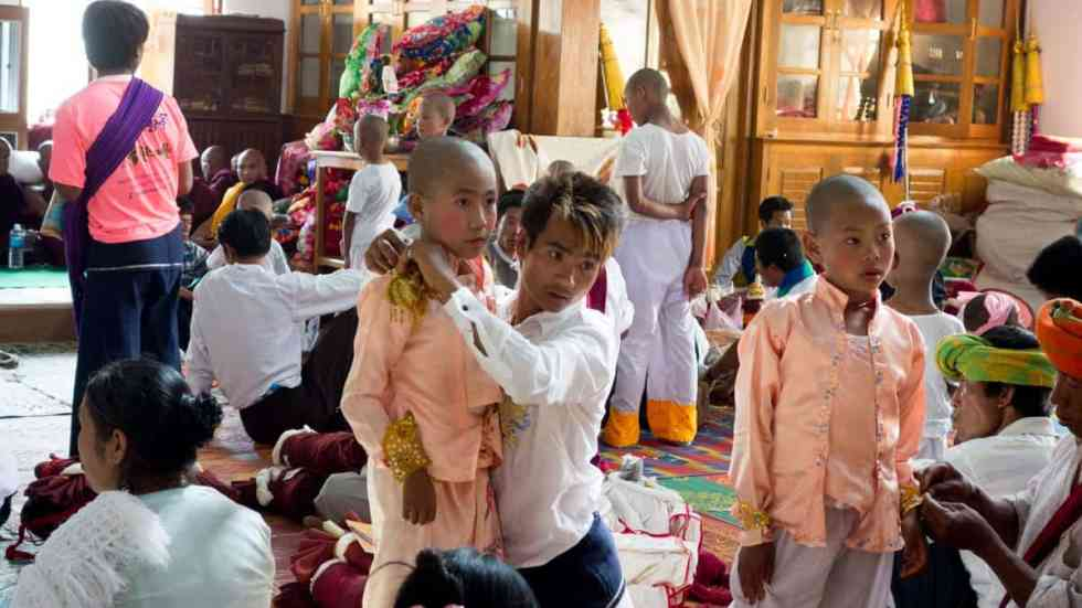 Boys disrobing at temple before getting monk robes
