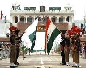 Soldiers of the Indian BSF and Pakistani Rangers hold their respective flags at Wagha border